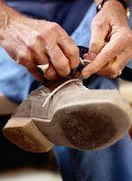 A man tying his bowling shoes.