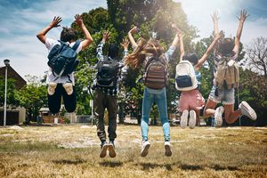 Students with backpacks jumping in unison