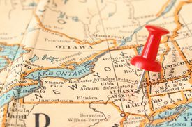 Pushpin pointing Albany city, New York state capital, over more than fifty years old map