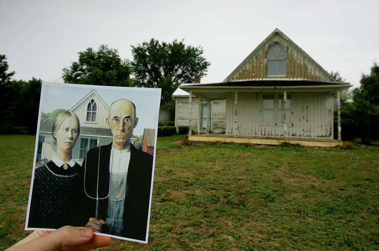 "Photo of Grant Wood's Painting ""American Gothic"" Held up in Front of the Gothic Revival House in Disrepair"