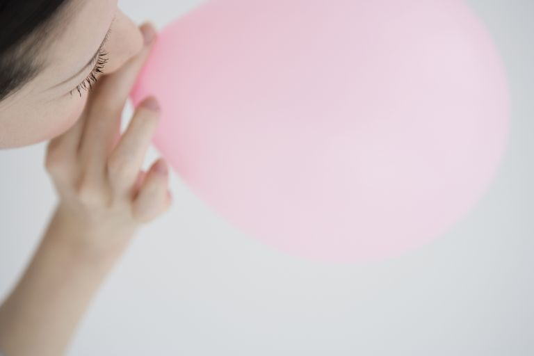 A girl blowing a balloon