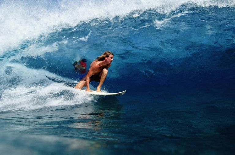 A surfer in a barrel, Tahiti
