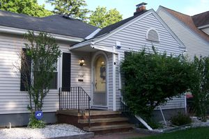small home with front gable, front door set into cross gable