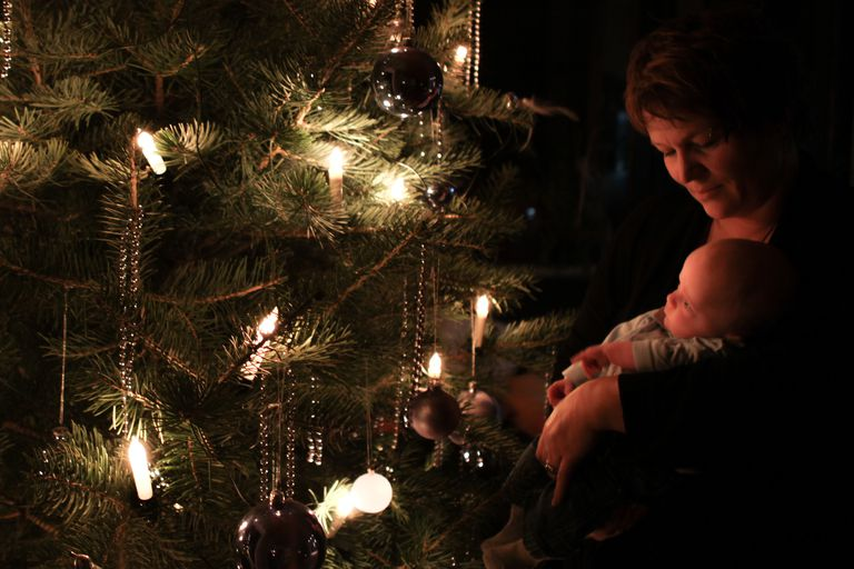 mother holding cute baby boy against christmas tree at night