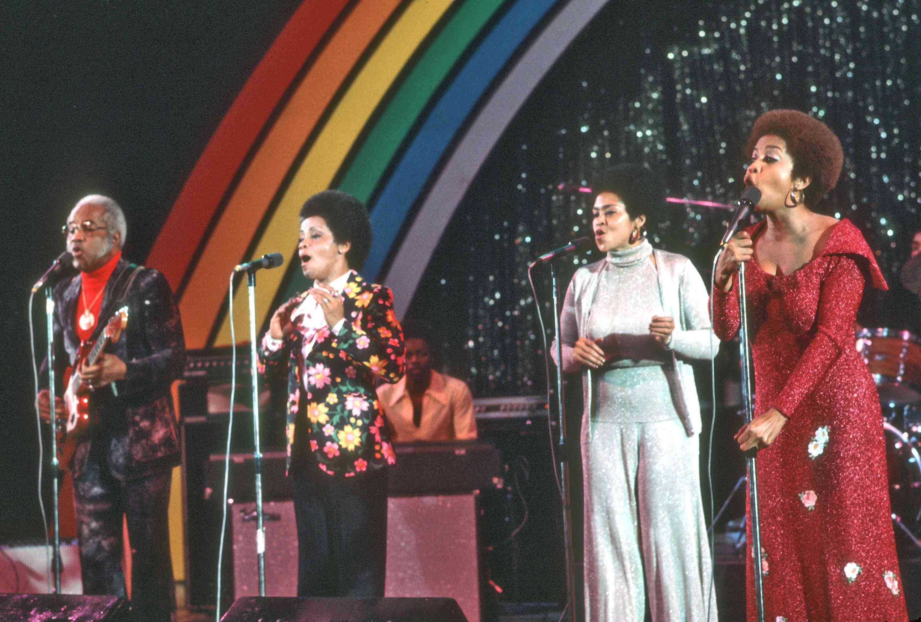 Four singers standing side by side at four separate microphones