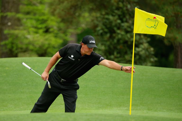 Phil Mickelson removing a flagstick at Augusta National during The Masters