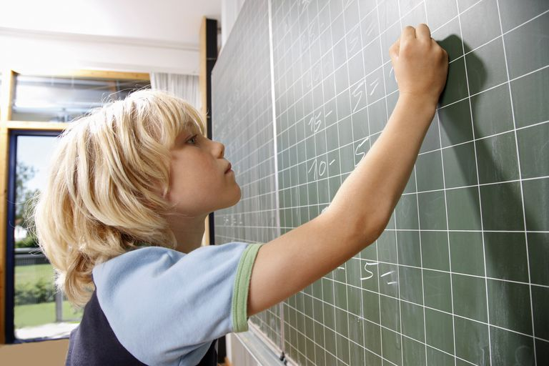 boy writing at blackboard