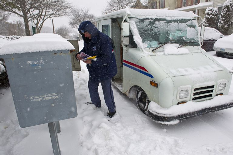 USPS mail carrier delivering mail on a snowy day