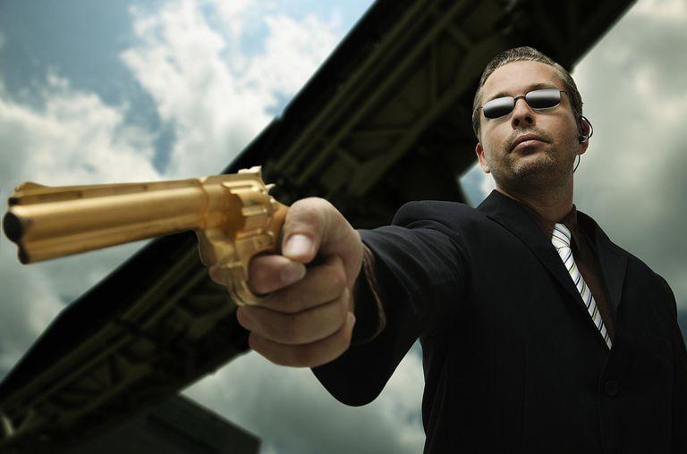 Varón apuntando con una pistola.