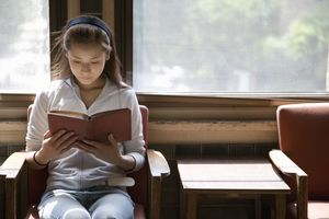Young woman sitting in chair, reading book
