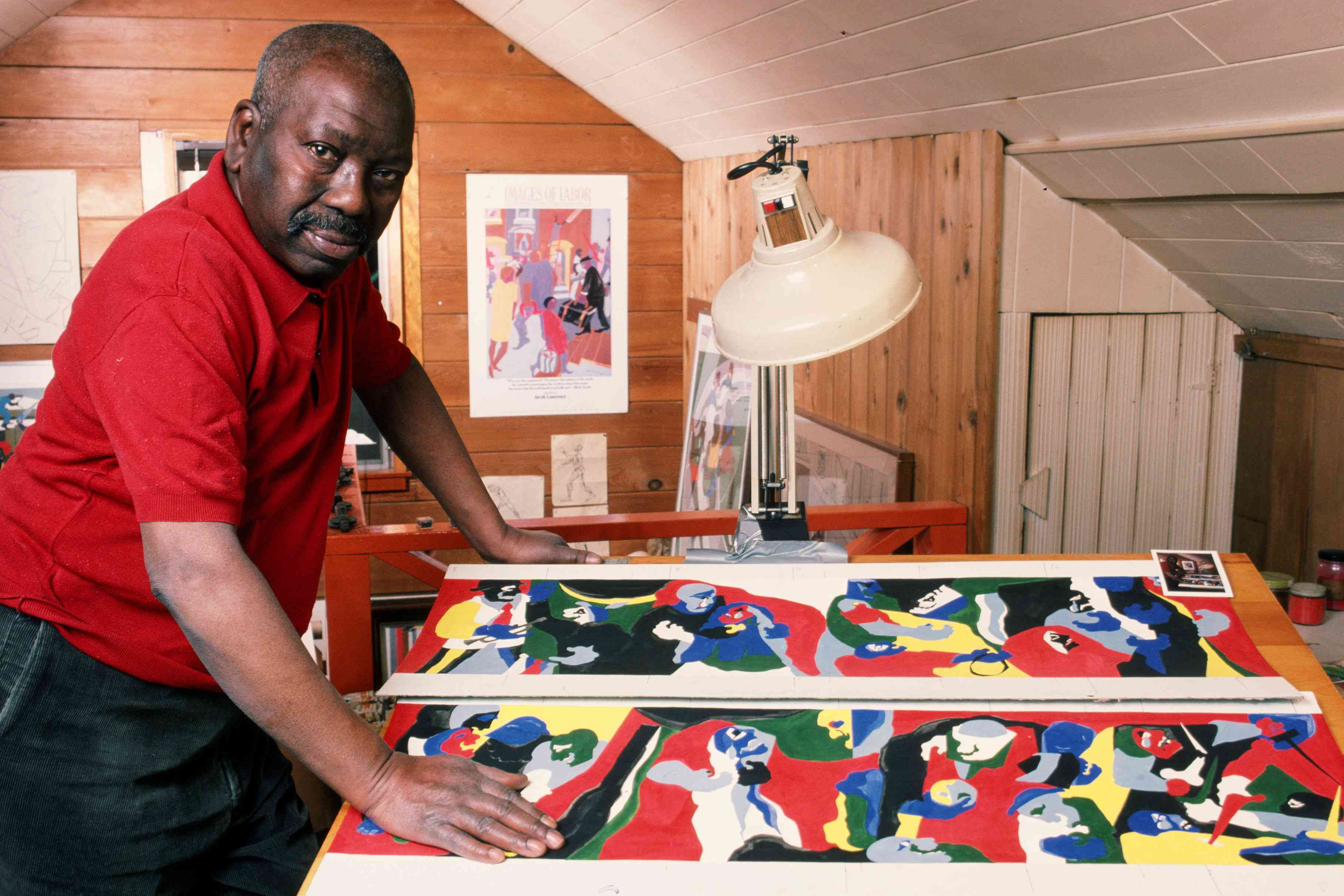 Artist Jacob Lawrence stands hunched over his work, a colorful painting