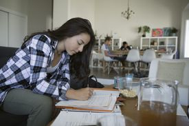 Teenage girl doing homework, studying at coffee table in living room