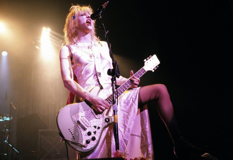 Courtney Love playing guitar on stage