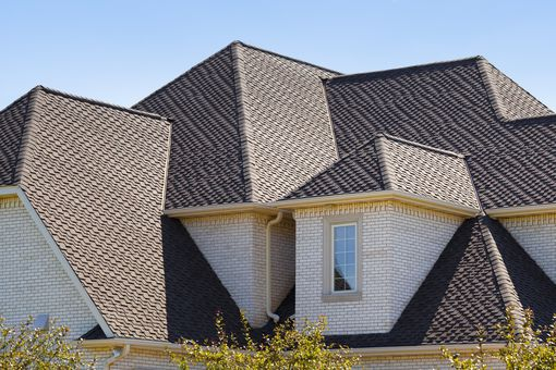 The angle of the sun pronouncing the intricacy of the roof shape and diagonal shingling