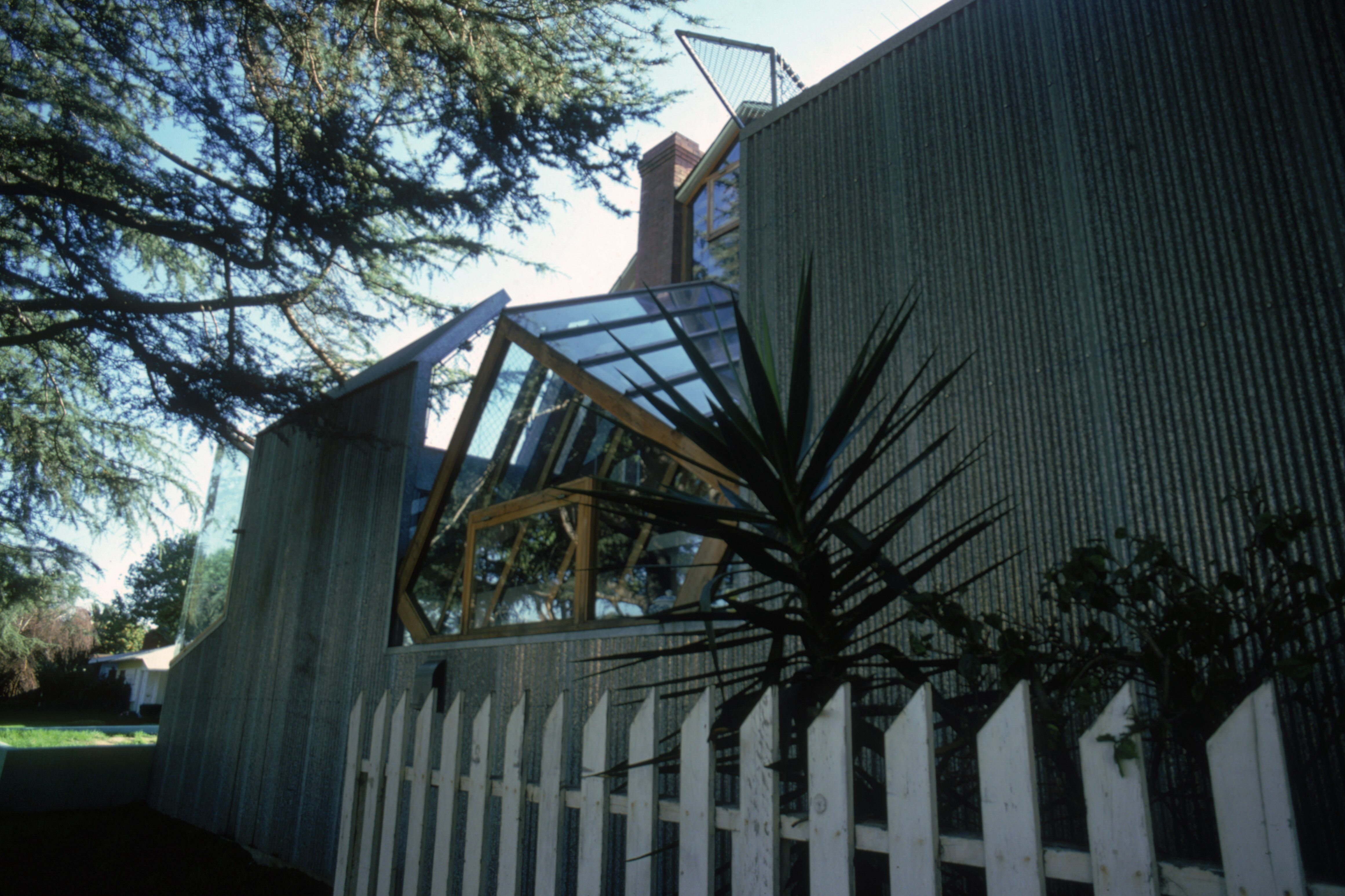 picket fence in front of corrigated metal panels and jagged window skylights