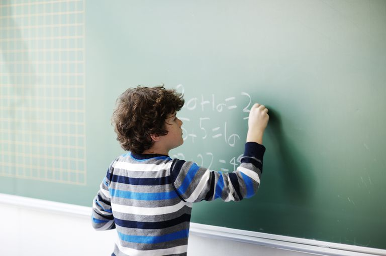 Boy writes math problems on chalkboard