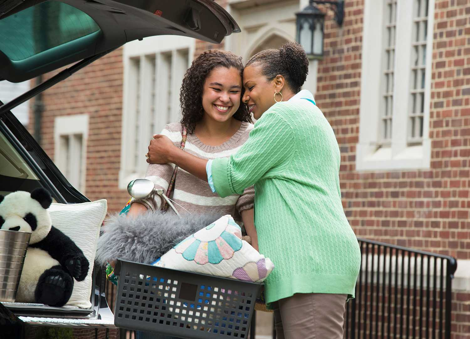 Mother and daughter hugging near car