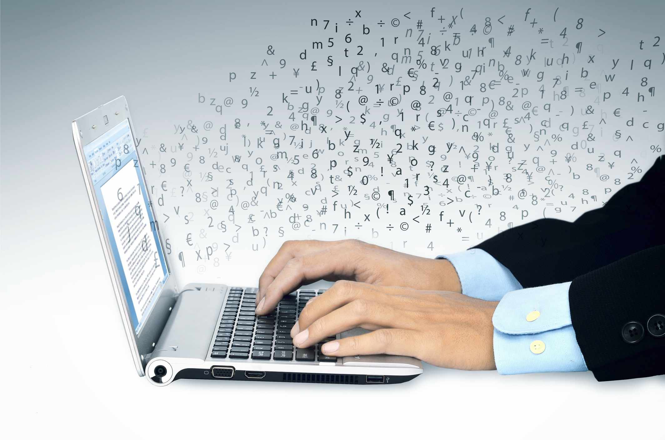Man's hands typing on laptop, using a word processing software.