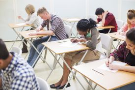 Students writing their GCSE exam in classroom