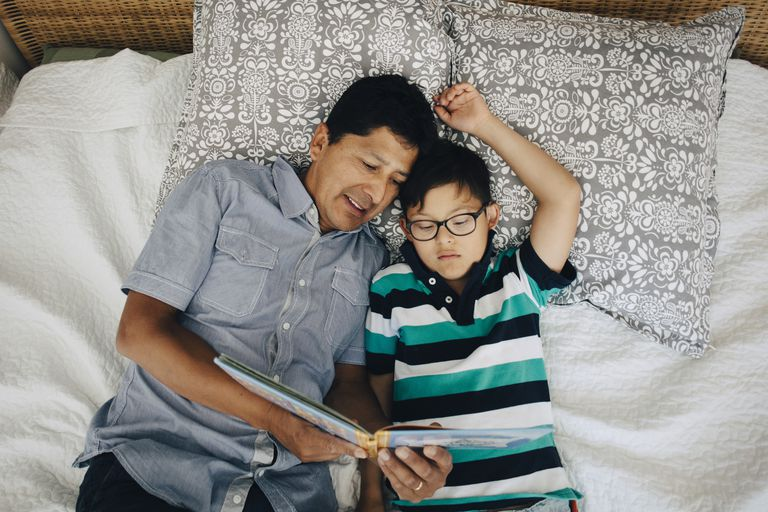 High angle view of father reading book to son while lying on bed at home