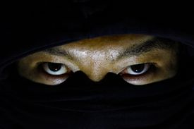 A ninja in the shadows staring out from behind a black mask.