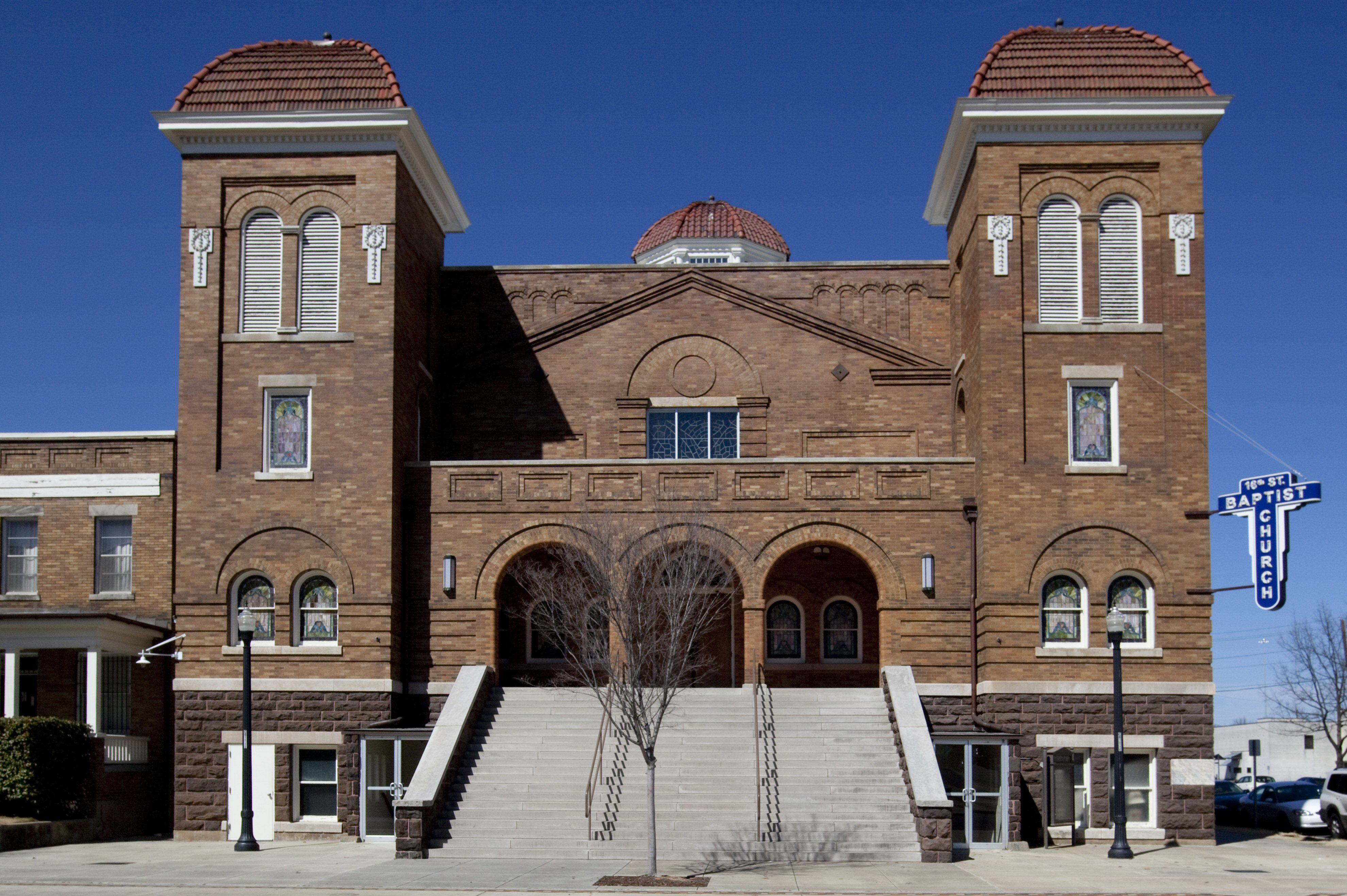 large brick building, symmetrical, two towers on either side of front gable with three arched entrances -- many stairs going up to the arches