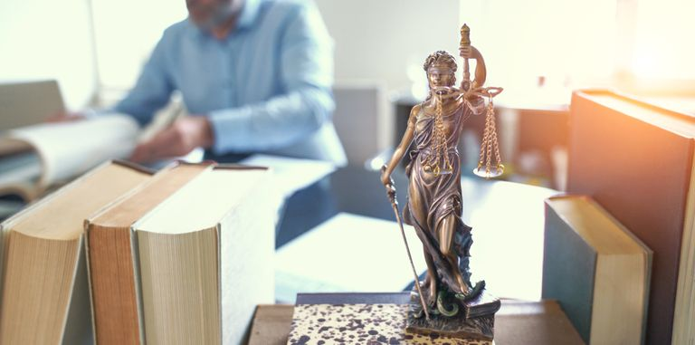 Close-Up Of Lady Justice On Table With Lawyer In Background At Office