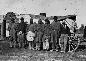 African Americans nicknamed contrabands before a signal tower in 1864.