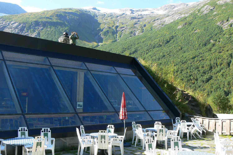 κεκλιμένο γυαλί στο εξωτερικό αίθριο με τραπέζια και καρέκλες με άτομα στην οροφή