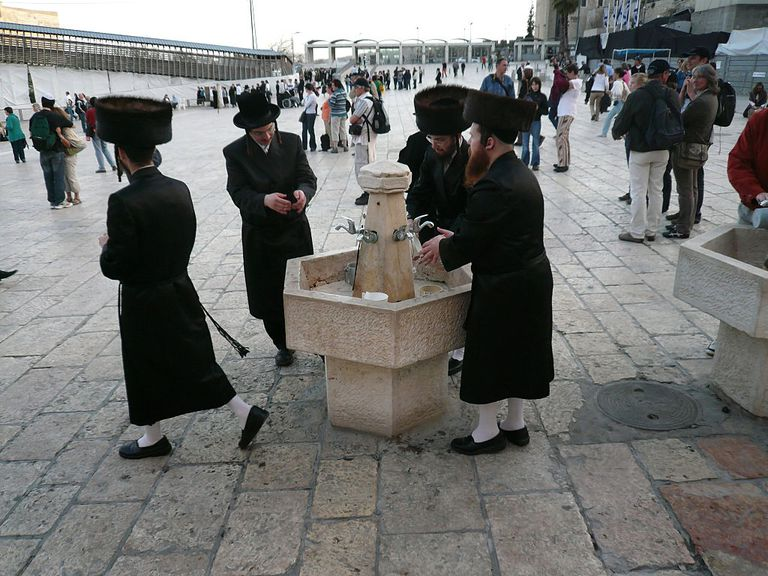 Four ultra-orthodox men washing their hands before attending shabbat prayers at the Westen Wall, in the Old City in Jerusalem.