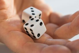 Two dice held in one hand, close up image.