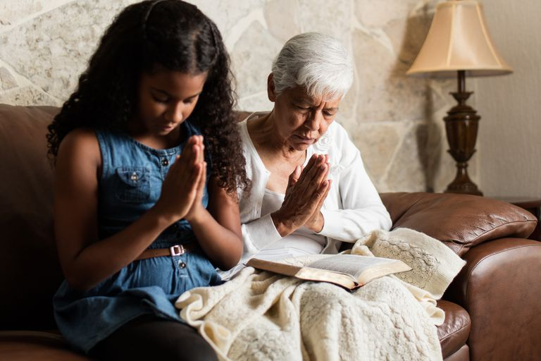Senior woman and girl sitting on sofa and praying