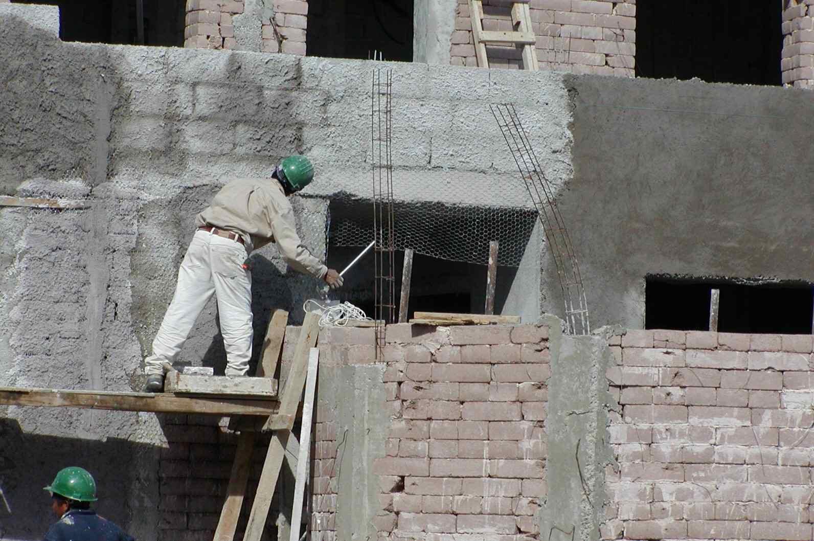 man in hard hat on scaffolding working on earth block wall
