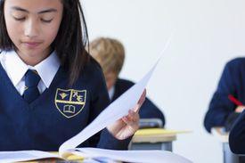 Children Wearing Uniforms Read at Their Desks