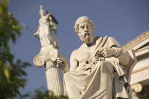 Statue of Plato outside the Hellenic Academy on a sunny day.