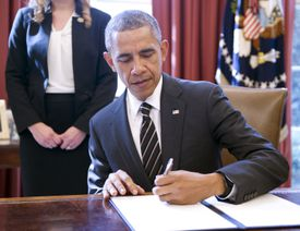 President Obama sitting at desk in oval office signing an executive order.