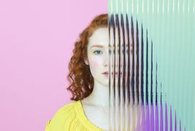 half of woman's face obscured by glass