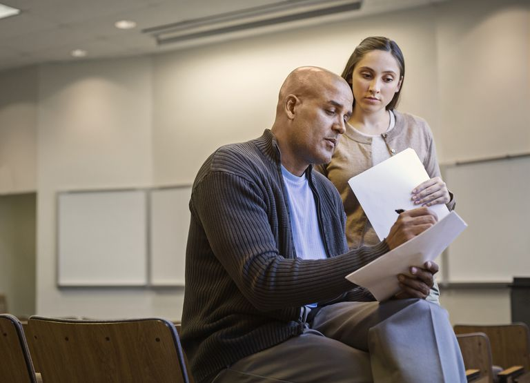 Professor and student reviewing essay in lecture hall