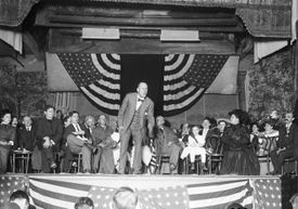 Black and white photo of a man speaking on a stage with a flag draped behind him