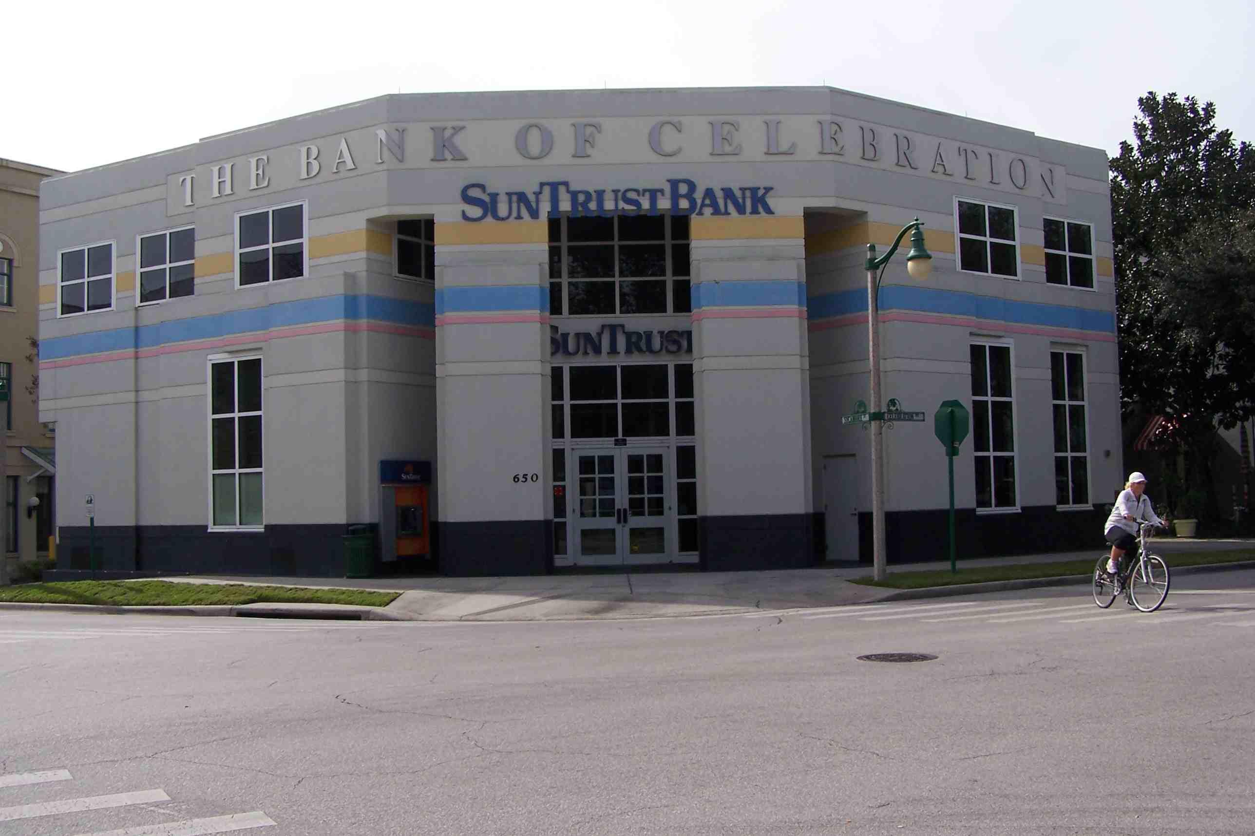Sun Trust Bank, The Bank of Celebration, con una fachada de tres lados, persona en bicicleta en una calle cercana