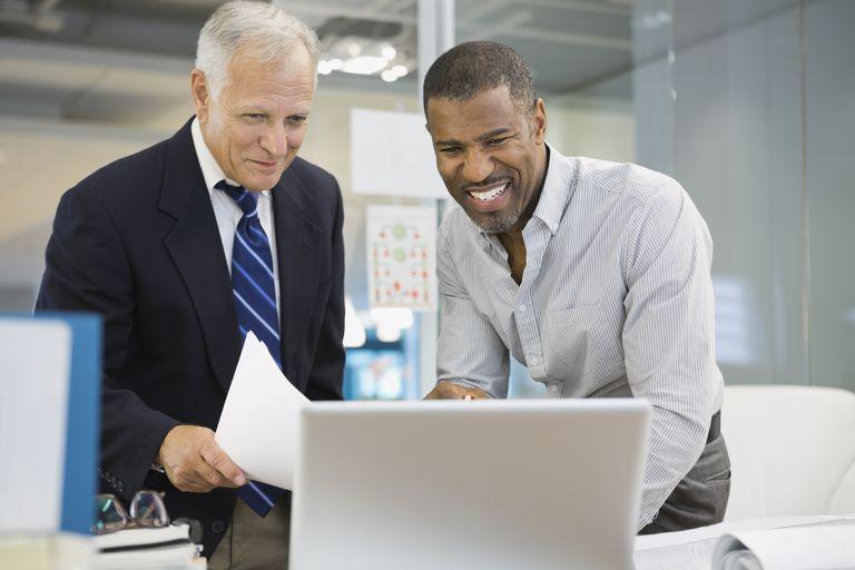 Businessmen working on laptop in office