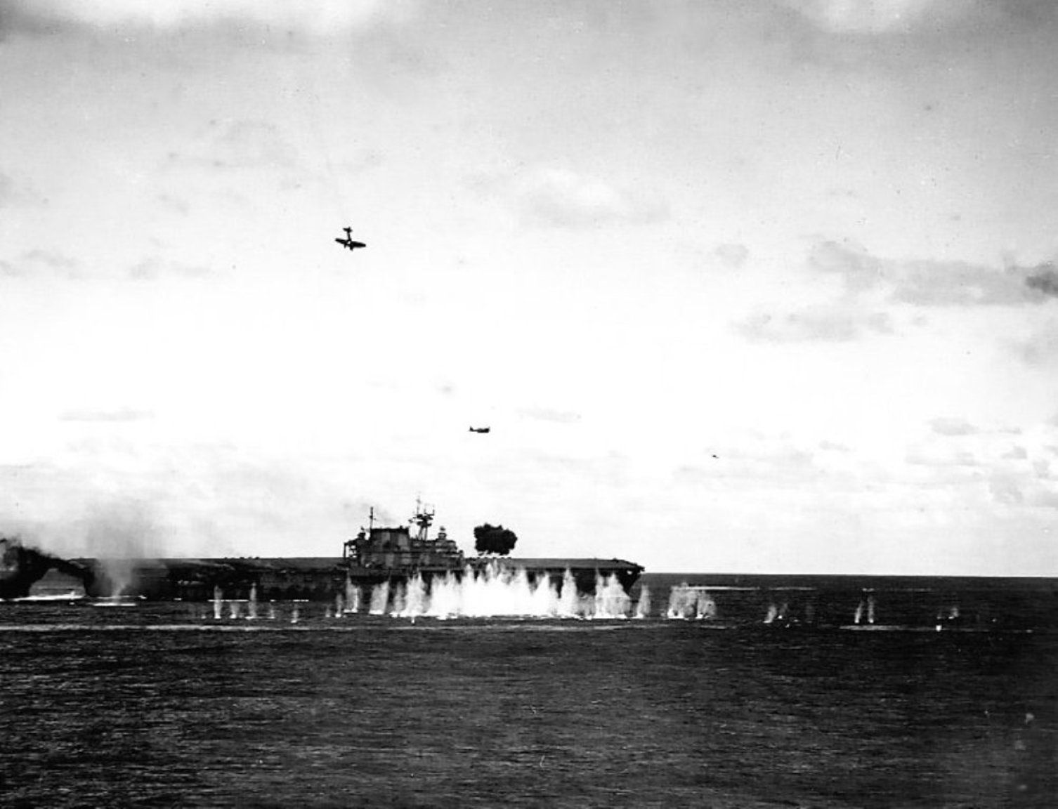 USS Hornet at sea being attacked by Japanese aircraft.