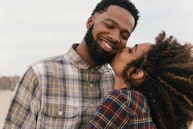 Romantic young couple kissing on beach, Coney Island, New York, USA