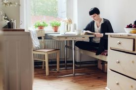 Female Student Reading A Book In Her Kitchen
