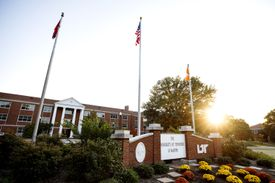 A two-story brick building with white pillars, with flagpoles in front and a brick sign with the UT Martin name