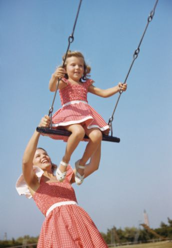 Mother pushing Daughter on Swing, matching outfits