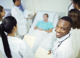 Doctor standing with residents in hospital room