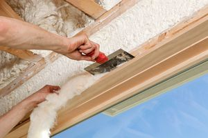 Person installing fiber glass insulation above a window.