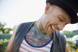 A laughing young man with tattooed chest looking down