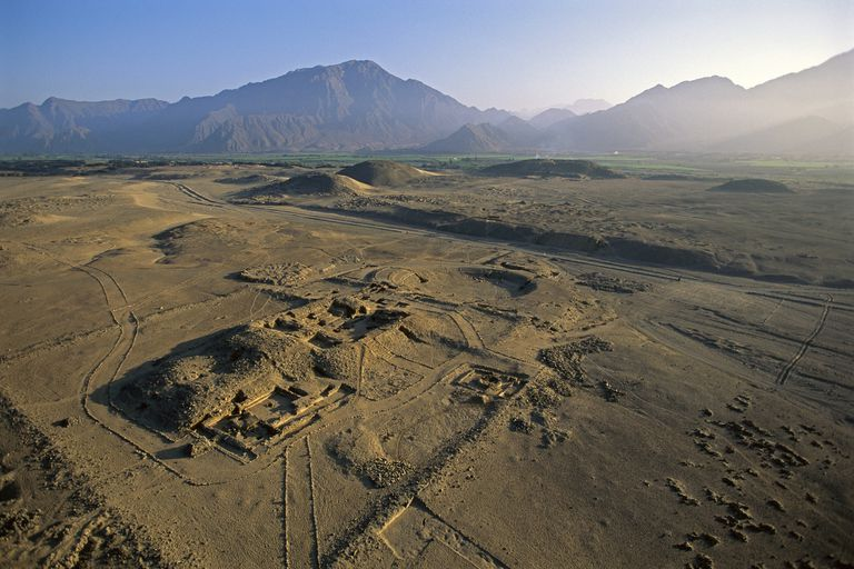 amphitheater with unexcavated pyramids of sacred city of Caral in background